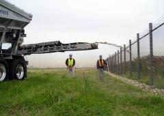 Ultra Stone Slinger placing rock along a fence line